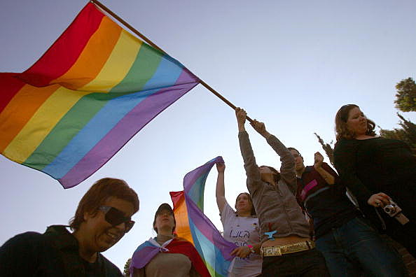 gay pride flag and crowd (Photo by Uriel Sinai/Getty Images)